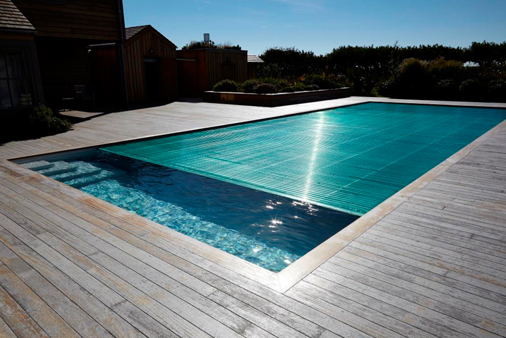 Natural materials meet contemporary design in a luxury outdoor swimming pool on the South Coast